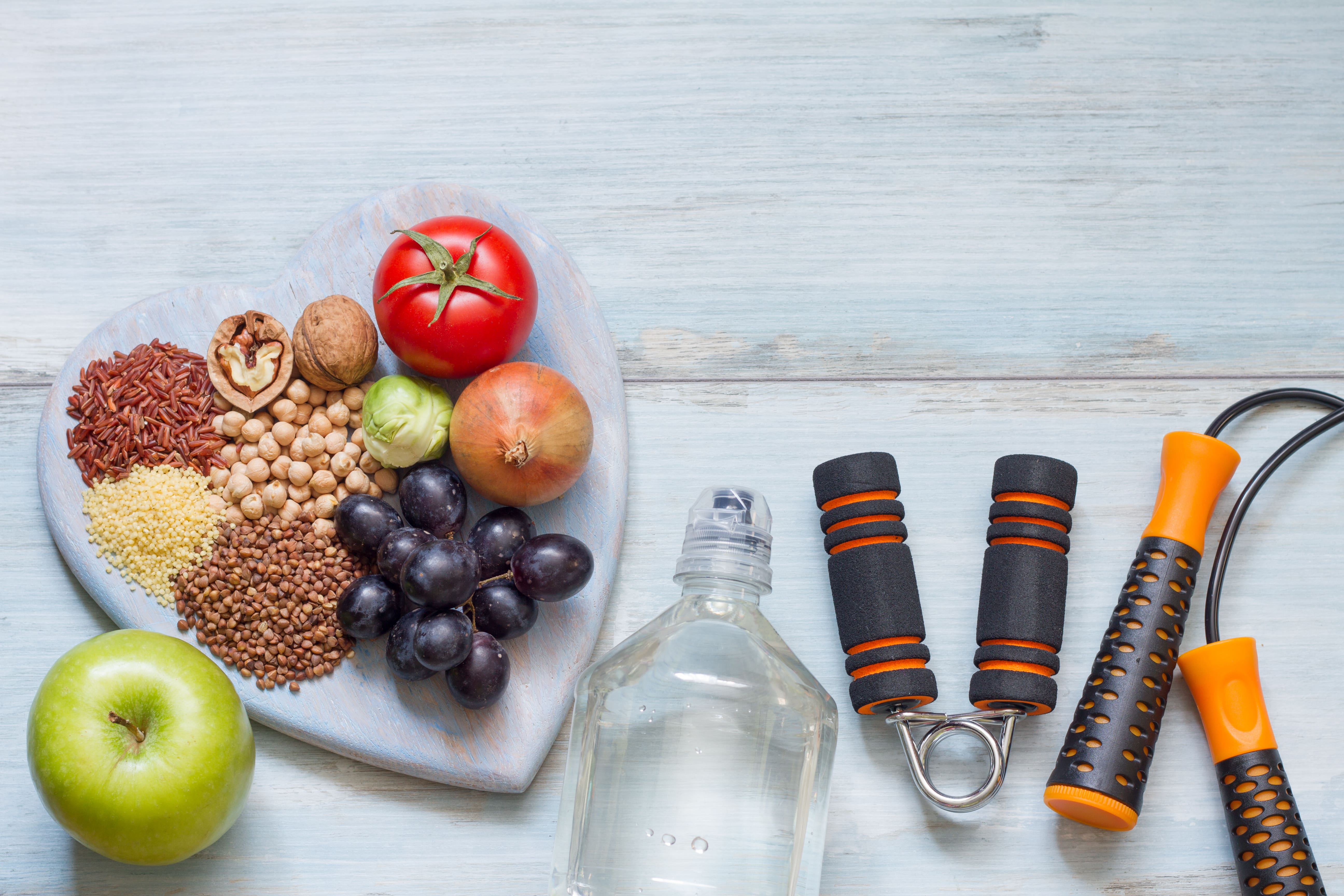 healthy fat loss tools including fruit, water, nuts, and exercise equipment